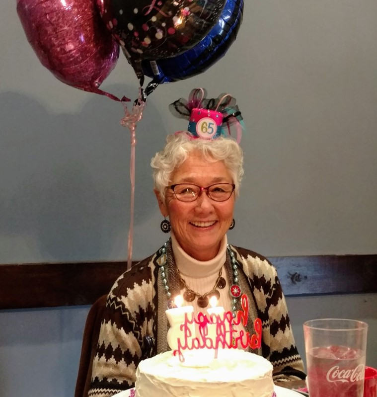 woman with birthday cake and balloons