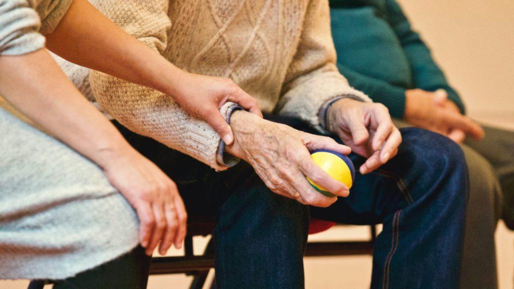 caregiver and elderly hands holding fruit